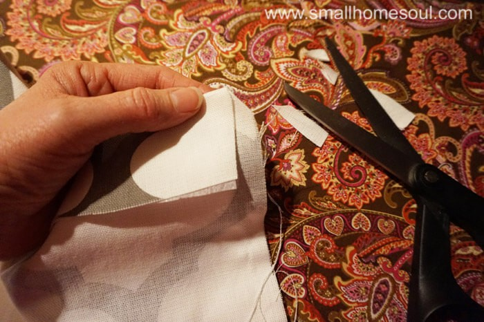 Clipping fabric corners before sewing hem of curtains.