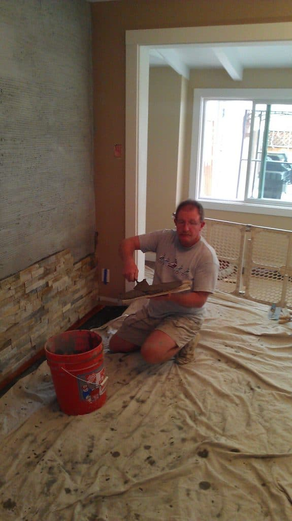 Buttering back of quartz tile with mortar to apply to wall.