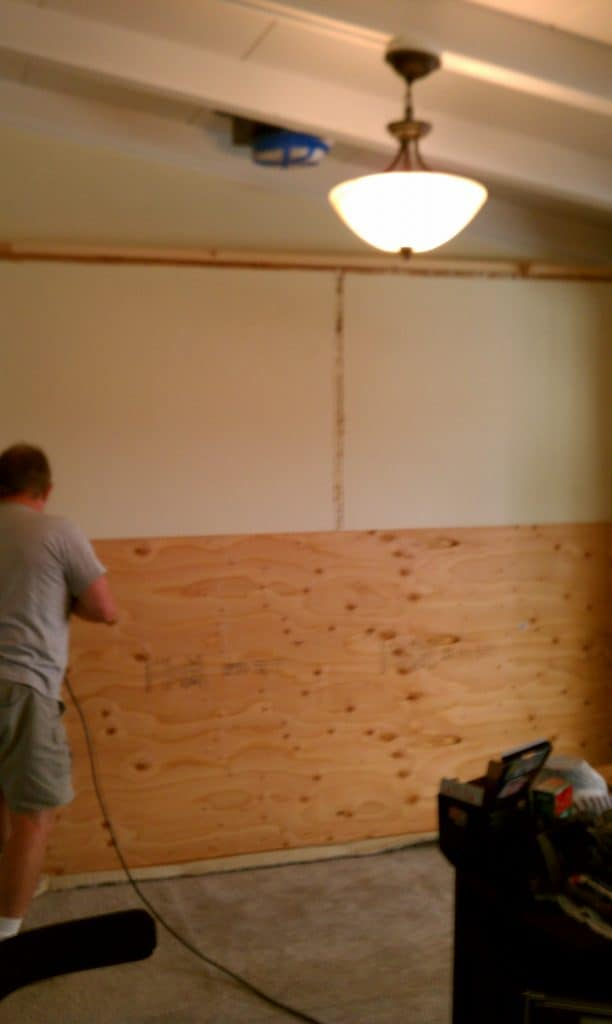 Screwing plywood to wall to prep for quartz wall insallation.