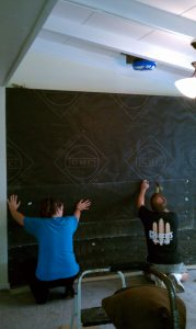 Attaching tar paper to plywood wall for quartz stone installation.