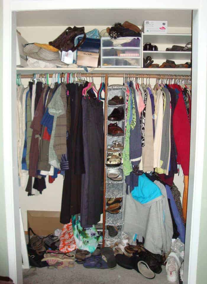 Before picture of bedroom closet with no doors and clothes disorganized with shoes in a heap on floor.