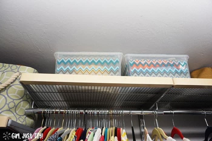 Top shelf of closet with two plastic bins.
