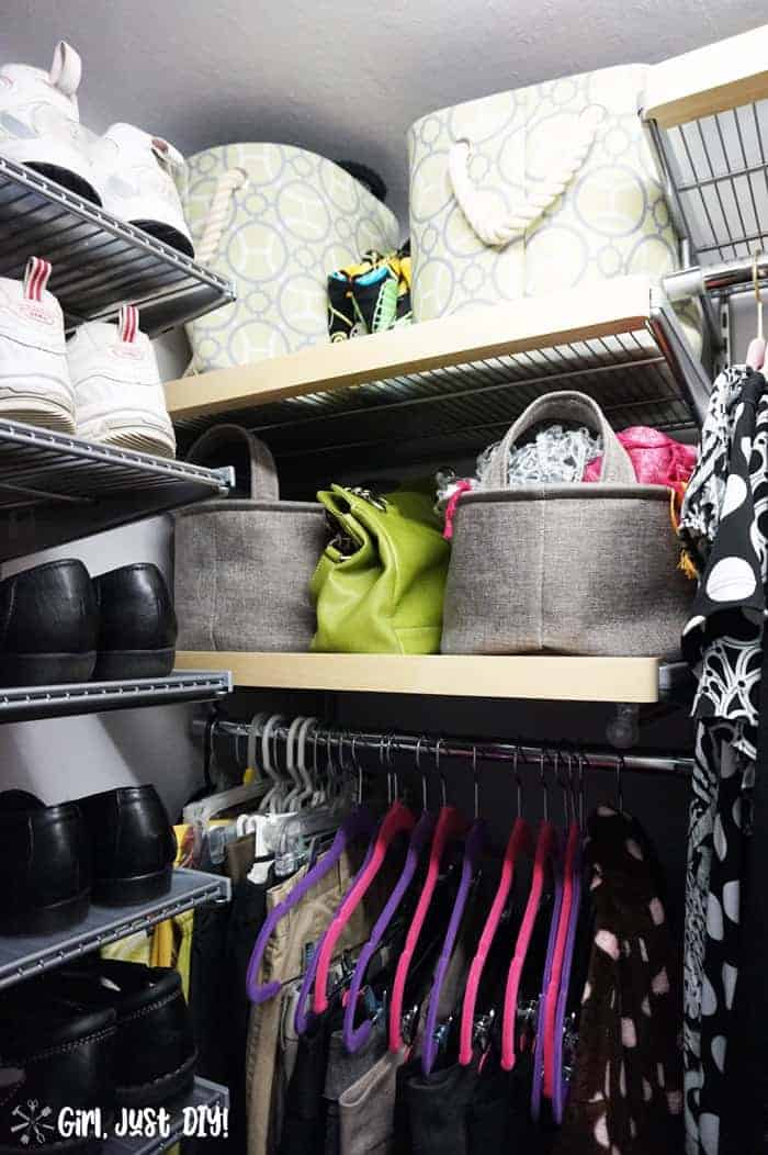 Fabric bins filled with scarves and purses on shelves between clothes and shoes.