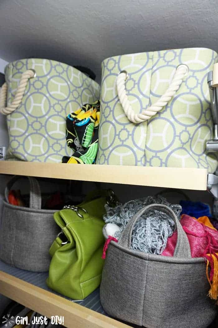 Fabric bins on closet shelves stuffed with scarves and purses.