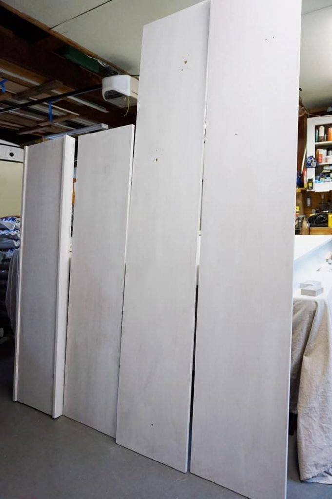 Pre-painted murphy bed pieces standing in garage.
