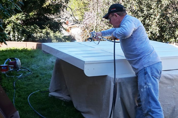 Man using sprayer to paint wood wall bed cabinet front