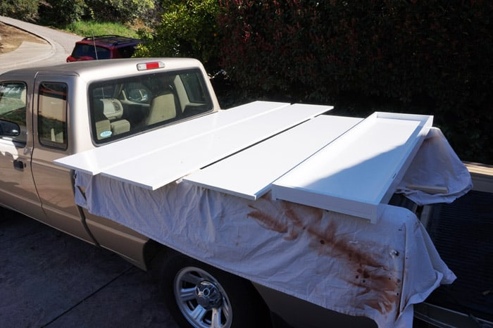 Sections of painted murphy bed drying on truck bed