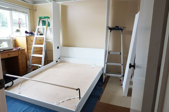 Ladders flank the partial assembly of the murphy wall bed
