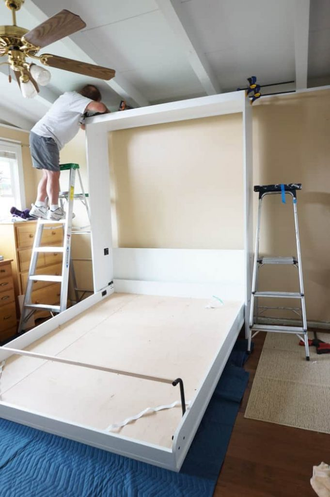 Man on ladder clamping murphy bed header to sides.