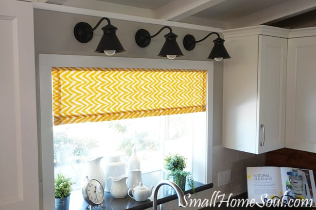 Goose neck lights over kitchen sink above yellow curtains.
