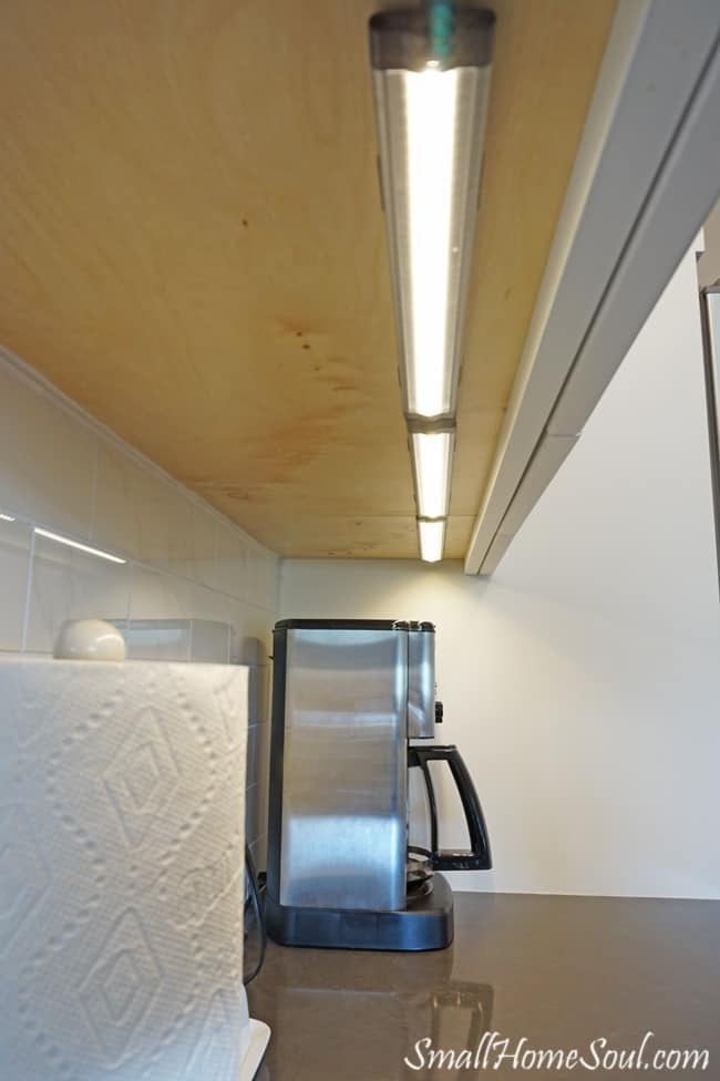 Under cabinet lighting above coffee pot and paper towels.