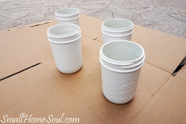 Jars with white paint dry as the rest of the mason jar utensil caddy is created.