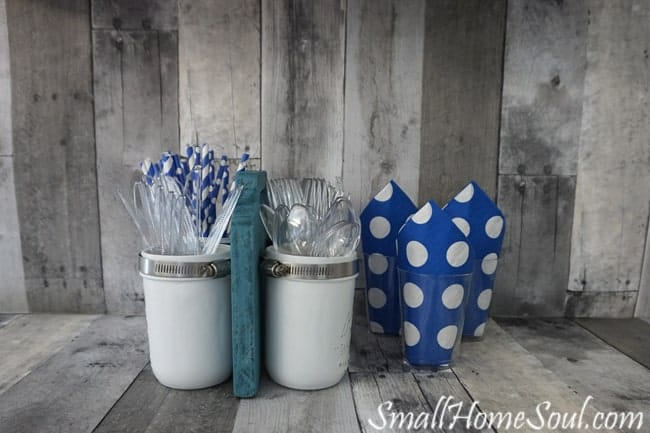 The mason jar utensil caddy is filled with plasticware and ready for a party.