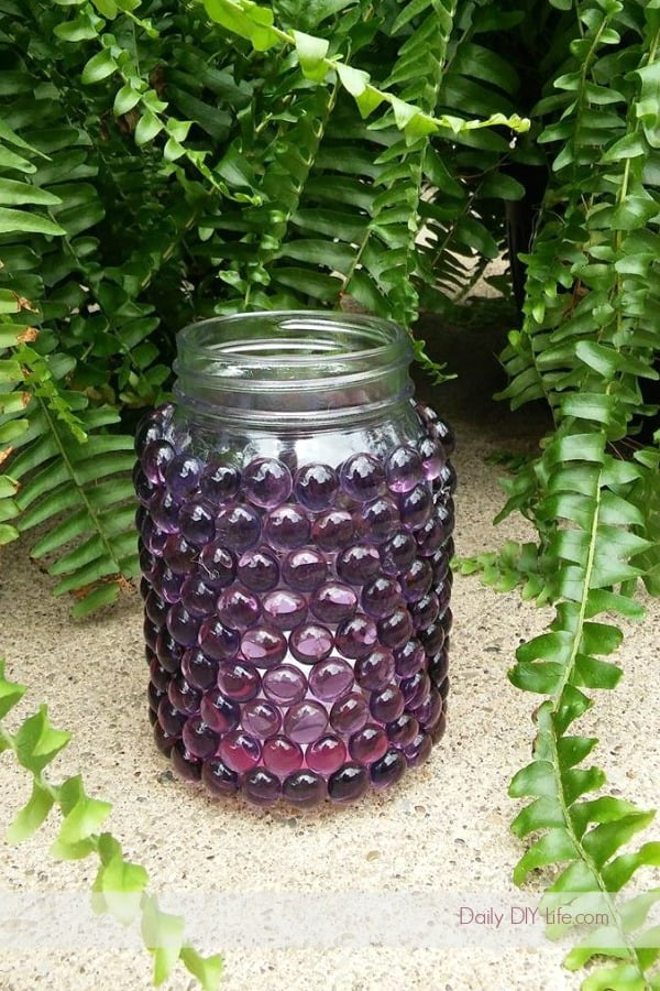 mason jar covered with purple glass beads in front of fern.