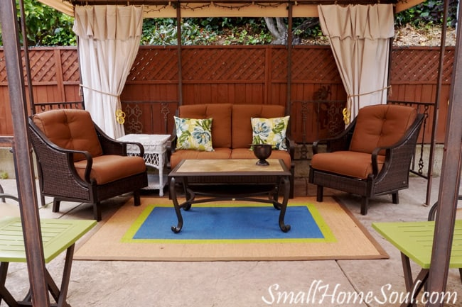 Drop cloth curtains on patio at back of gazebo with patio furniture placed around patio rug.