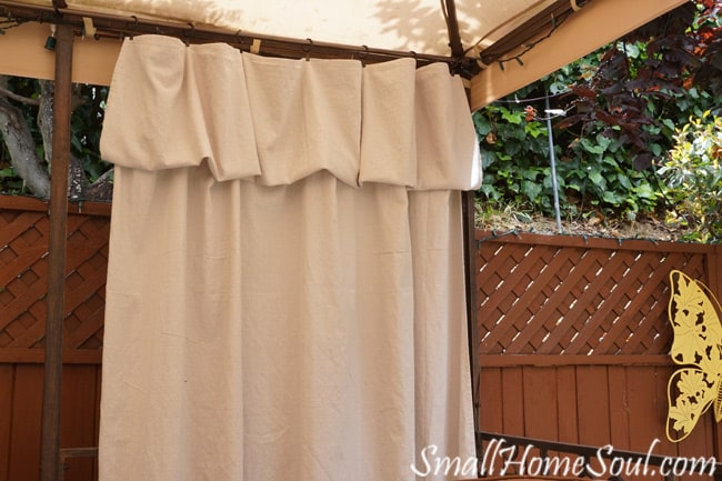 Drop cloth hung on curtain clips with the top folded over into a valance.