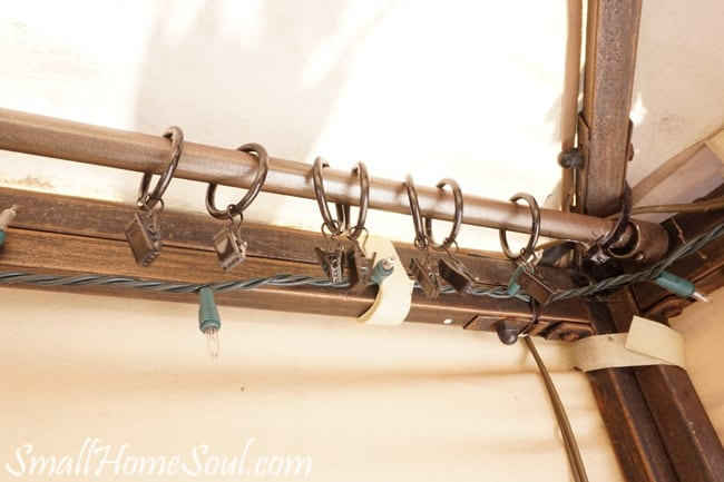 Curtain rod attached to gazebo with empty curtain clips.
