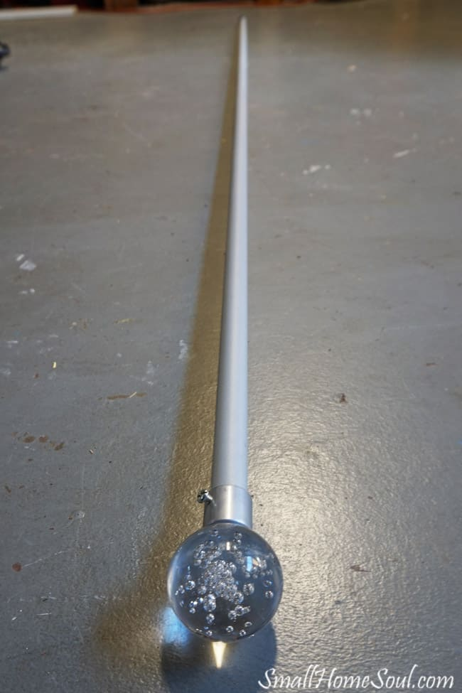 Rod for drop cloth curtains on floor of garage before painting it.
