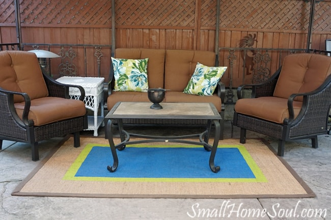 Painted seagrass rug on the patio with blue and green brightens up the seating area.