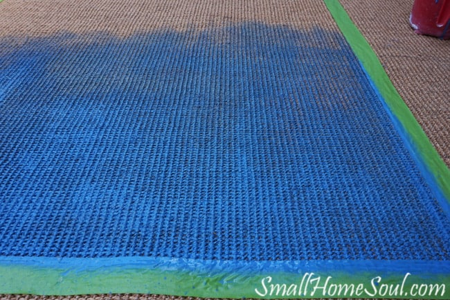Painting a seagrass rug with blue in the center.