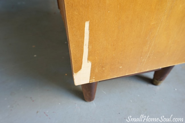 Side of mid-century modern dresser with missing veneer.