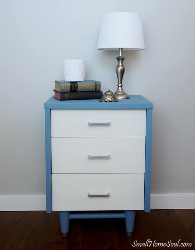 Completed blue and white mid-century modern dresser topped with a lamp and books.
