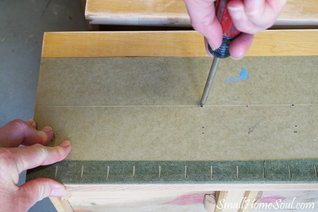 Poking a scratch awl into a green template on top of dresser drawer
