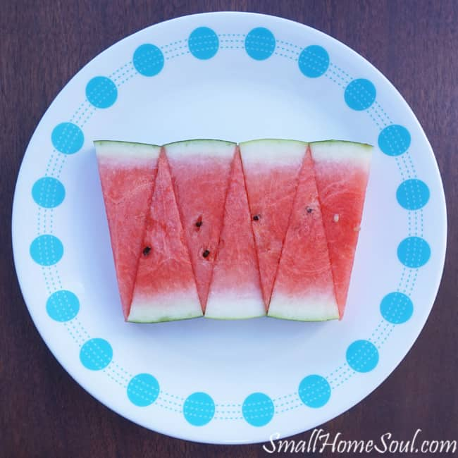 Fresh watermelon in an artsy display on a blue and white plate.