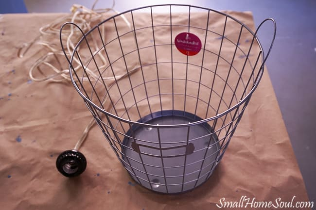 Wire basket and light kit on butcher paper.