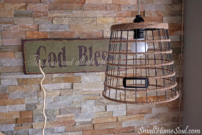 DIY Hanging light hanging in front of quarts wall and God Bless sign.