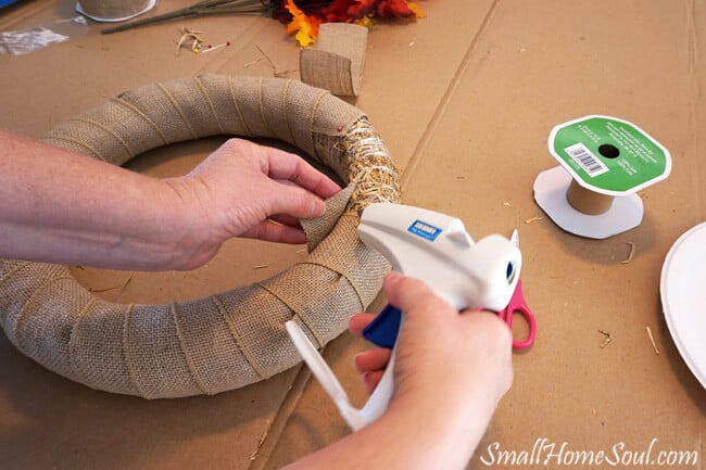 Hotgluing burlap ribbon to straw wreath form.
