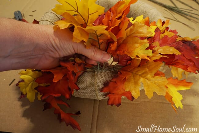 hand pushing maple leaf stems into wreath form.