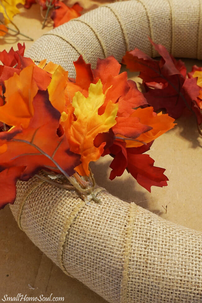 Faux maple leaf stems inserted into burlap wreath.