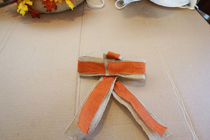 burlap and orange ribbons crossing over bows