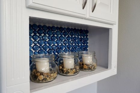 Blue glass backsplash in TP cabinet with candles in jars.