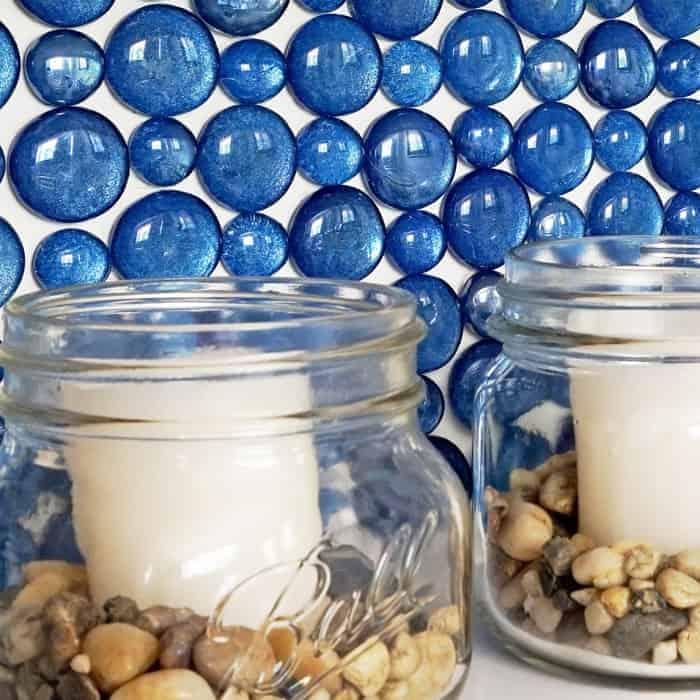 Glass backsplash behind candles in mason jars.