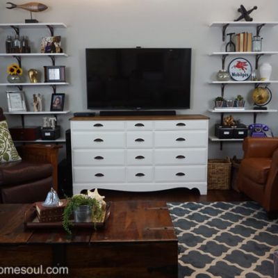 Living room shelves installed and decorated flank the tv and console.