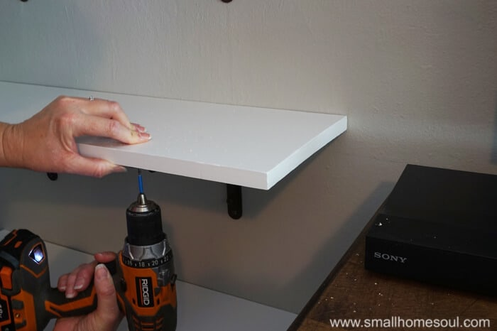 Screwing shelf board to shelf bracket with cordless drill while hand holds steady