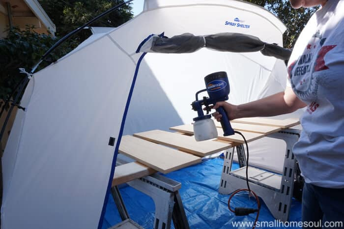 paint tent with shelves on sawhorses getting a coat of white paint.