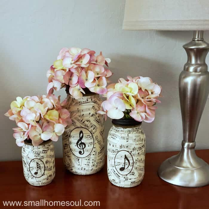 Three sheet music mason jars on table filled with hydrangeas next to lamp.