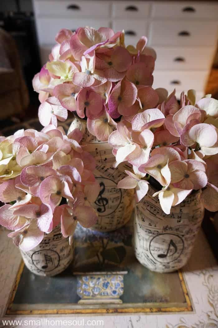 Sheet music mason jar vases filled with faux hydrangeas on coffee table.