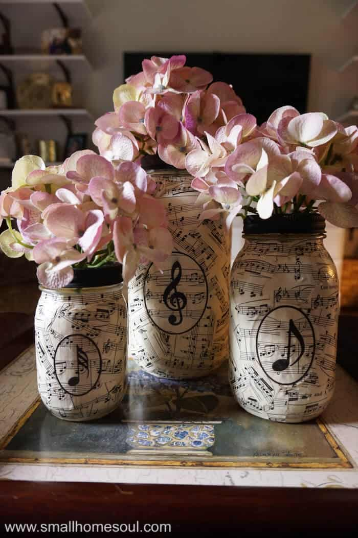 Music sheet mason jar vases filled with colorful hydrangea flowers in tray on coffee table.