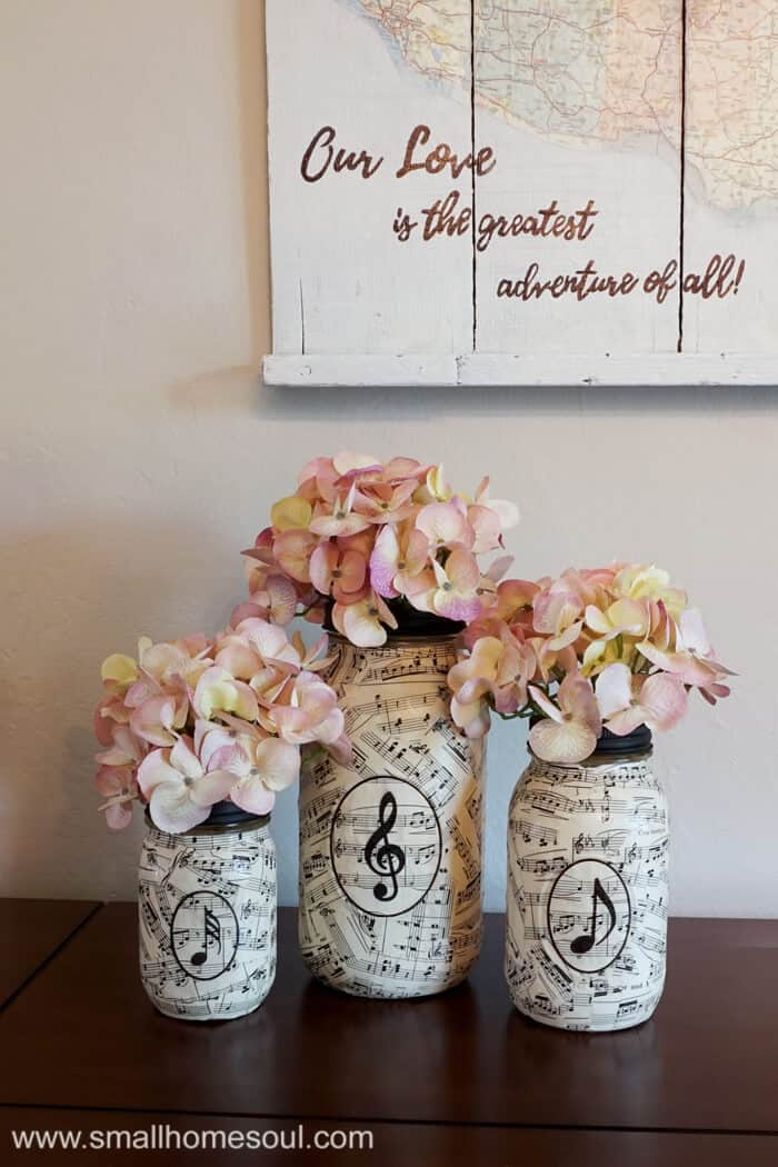 Music sheet mason jar vases filled with hydrangea on dining room buffet.