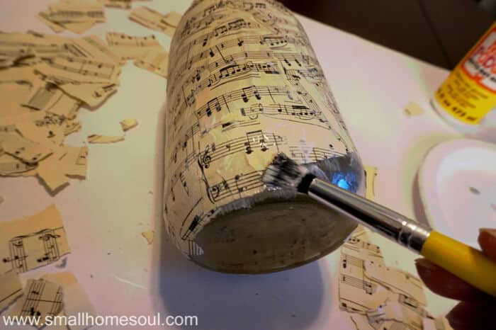 Paintbrush with decoupage gluing on torn sheet music to mason jar.