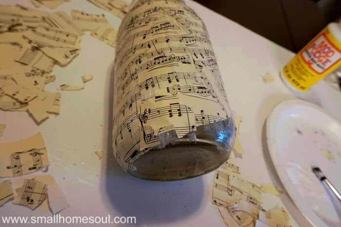 mason jar with torn sheet music decoupaged on sides.
