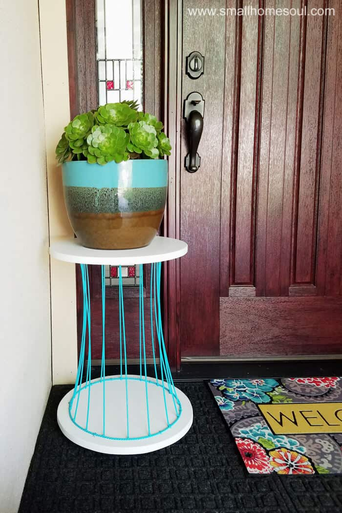 Pretty blue and white outdoor plant stand by front door on porch.