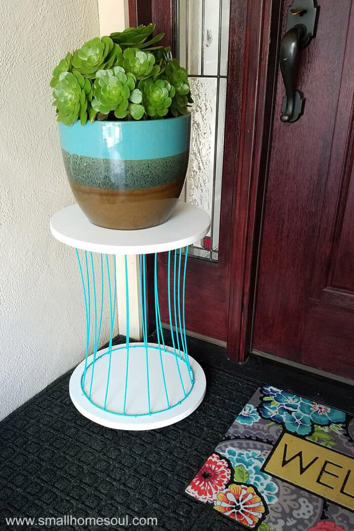 Newly finished outdoor plant stand on porch with a potted plant by front door.