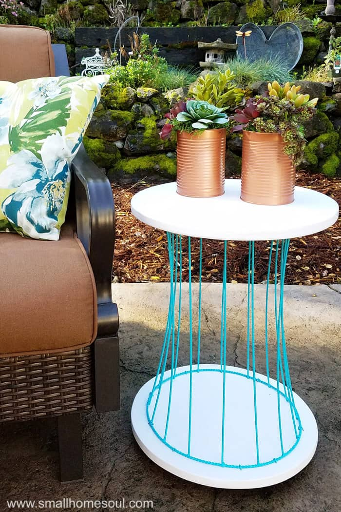 Outdoor plant stand as a side table on patio.