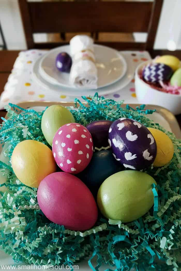 Easter table decorations with colorful eggs on a cake stand.