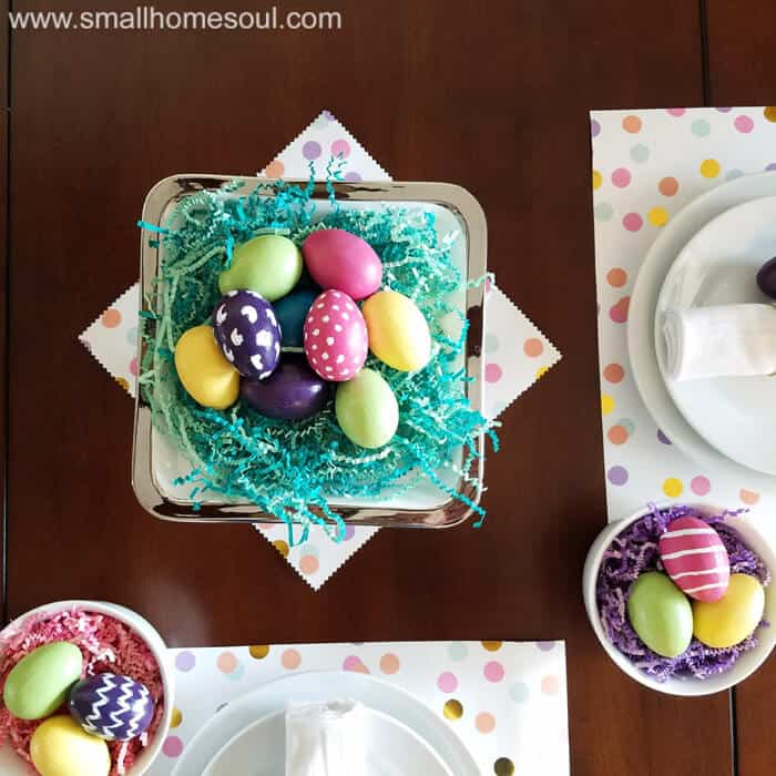 Easter table decorations looking down at colorful eggs on a cake stand.
